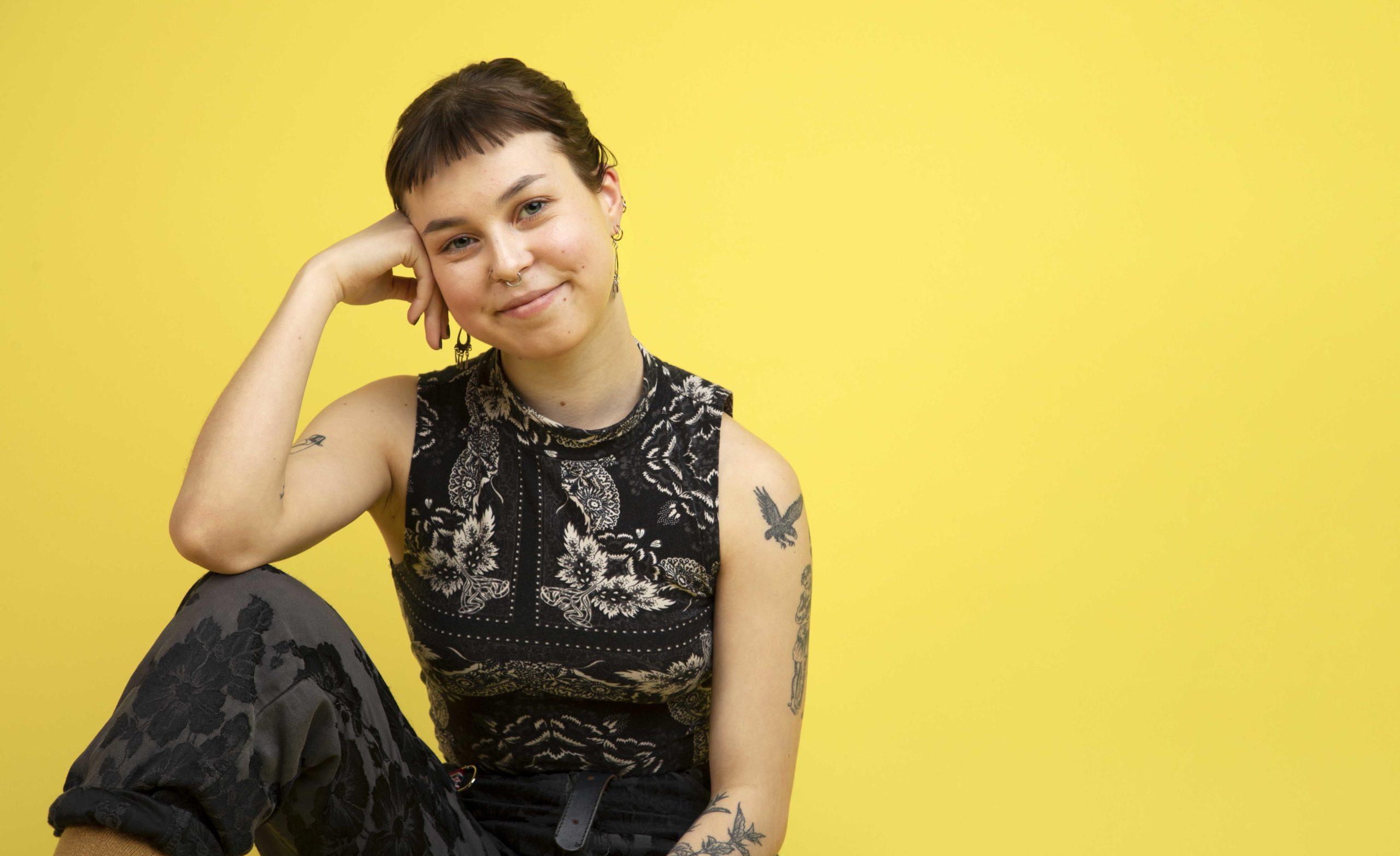 Nainen istuu ja hymyilee keltaisen taustan edessä