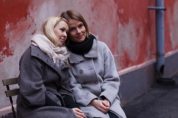 Kaksi naista tukee toisiaan punainen seinä taustalla
