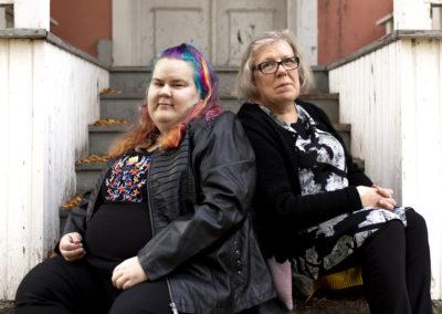 Vakavailmeiset äiti ja tytär istuvat portailla
