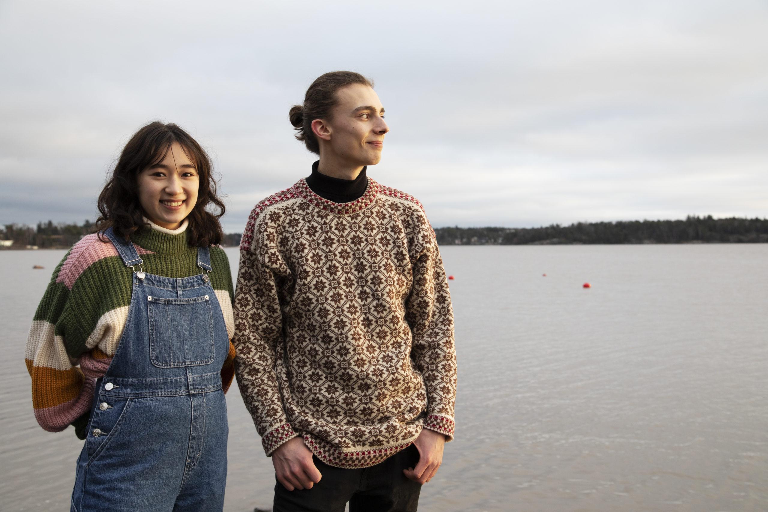 Kaksi hymyilevää nuorta veden äärellä