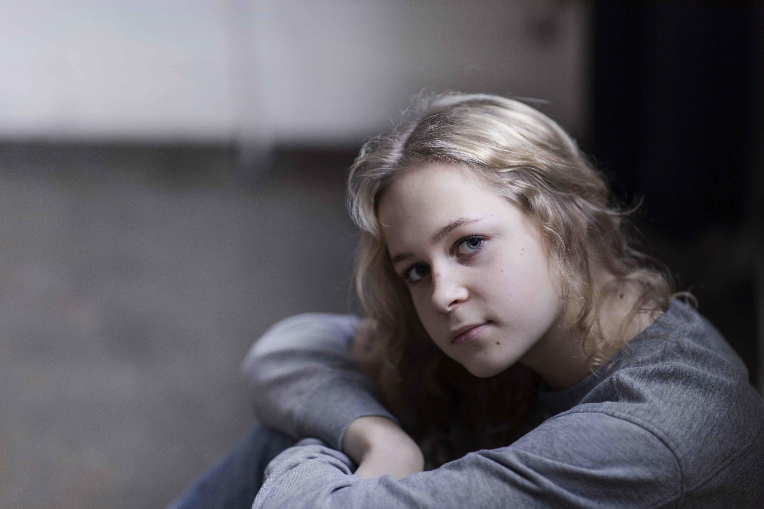 Vakavailmeinen tyttö istuu lattialla